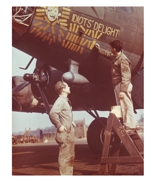 Usaaf crewman prepares to load bombs on b-17 flying fortress at station in england july 1943